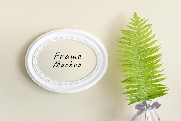 Bewerkbare psd-mockup met rond ovaal horizontaal frame en bos wilde varenblad in glazen vaas