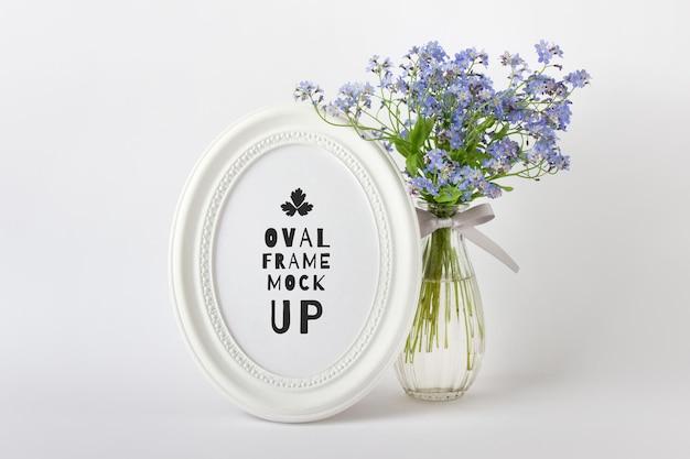 Bewerkbare psd-mockup met wit ovaal rond verticaal frame en blauwe zomerbloemen