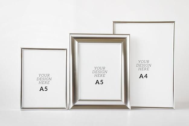 Bewerkbare psd-mockupsjabloon met drie zilveren metalen lege frames op witte achtergrond.