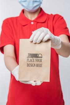 Bewuste jonge levering die een medisch masker draagt en een papieren zakmodel houdt