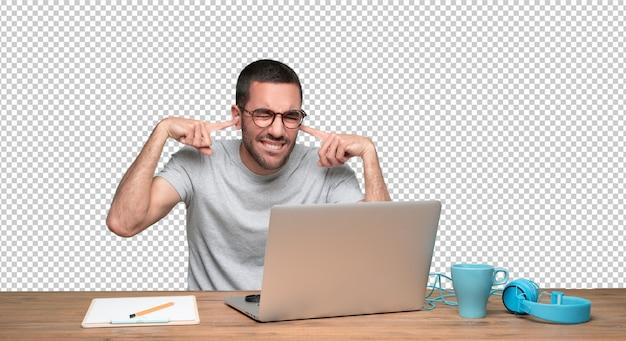 Bezorgd jonge man zit aan zijn bureau en die betrekking hebben op zijn oren met zijn handen