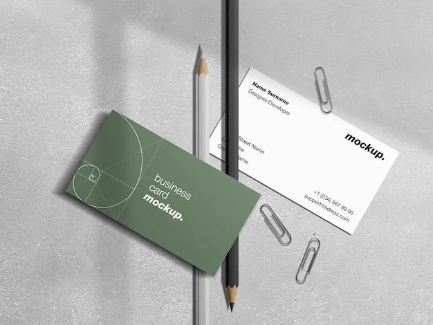 Biglietti da visita con matite, graffette e mockup di sovrapposizione di ombre