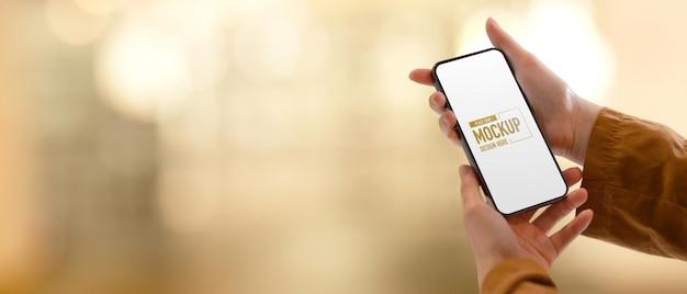 Bijgesneden schot van vrouwelijke handen met behulp van smartphone omvatten uitknippad scherm in wazig
