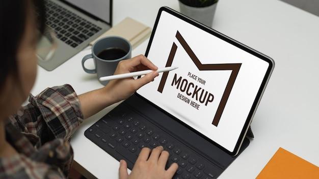 Bijgesneden schot van vrouwelijke werken met mock-up digitale tablet
