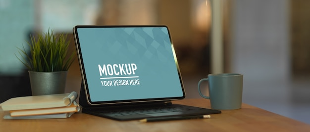 Bijgesneden schot van werkruimte met mock up digitale tablet, toetsenbord en notebooks op houten tafel