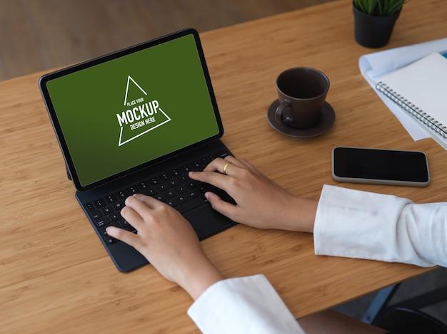 Bijgesneden schot van zakenvrouw typen op tablet toetsenbord op houten tafel