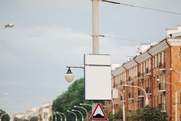 Bilbard met veelkleurige reclame en verlichting staat op straat bij daglicht, foto hieronder