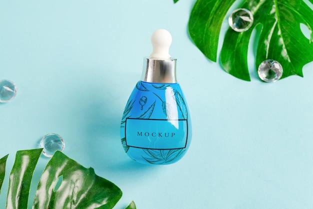 Blauwe flessen met cosmetica natuurlijke etherische olie of lotion met tropische groene bladeren.