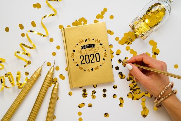 Bloc de notas y accesorios dorados con vista superior de la mano