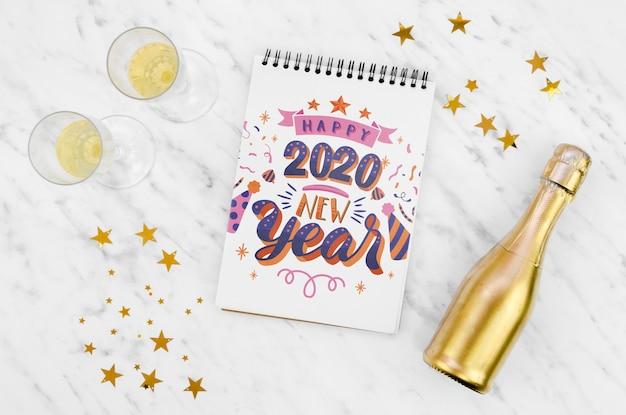 Bloc de notas blanco con cita de feliz año nuevo 2020 y botella de champán dorada