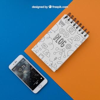 Blocco note e smartphone su sfondo arancione e blu