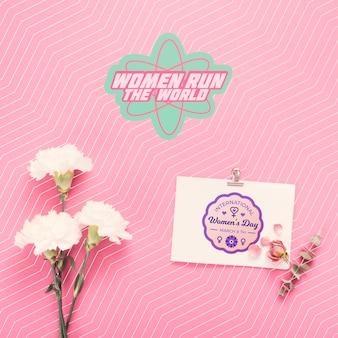 Bloemen en kartonnen model op roze achtergrond