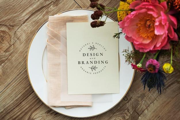 Bloemenboeket met een kaartmodel op een witte plaat