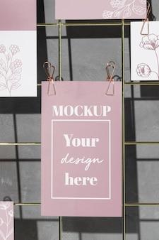Bloemenkaarten die aan rasterdraadbord hangen met roze clips