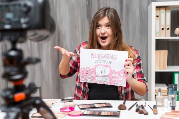 Blogger sosteniendo papel de maqueta