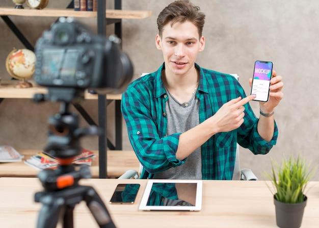 Blogger de tiro medio sosteniendo teléfono de maqueta
