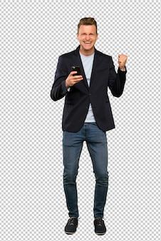 Blonde knappe man met telefoon in overwinningspositie