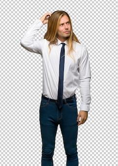 Blonde zakenman met lang haar die twijfels hebben terwijl het krassen van hoofd