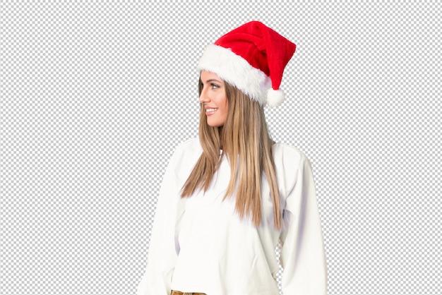 Blondemeisje die met kerstmishoed aan de kant kijken