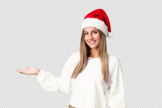 Blondemeisje die met kerstmishoed copyspace denkbeeldig op de palm houden