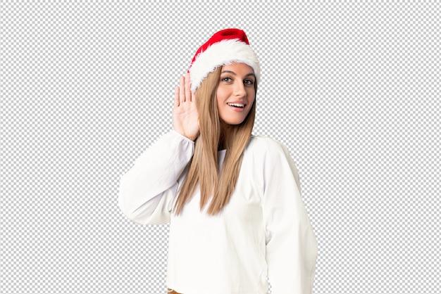 Blondemeisje die met kerstmishoed iets luisteren