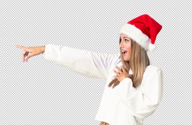 Blondemeisje die met kerstmishoed vinger aan de kant richten