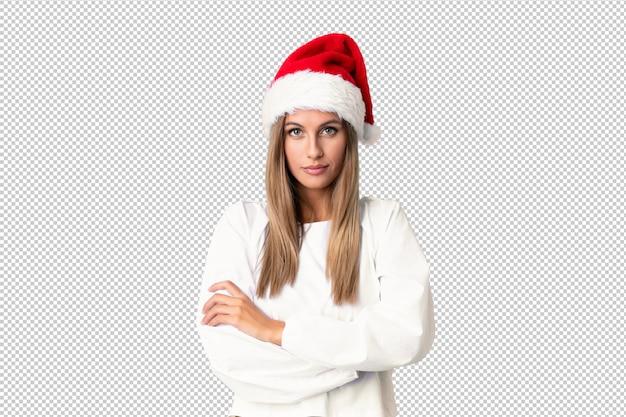 Blondemeisje met kerstmishoed die gekruiste wapens houden