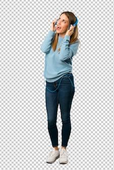 Blondevrouw die met blauw overhemd aan muziek met hoofdtelefoons luisteren