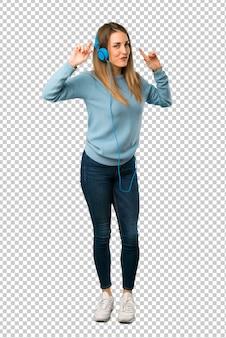 Blondevrouw met blauw overhemd die aan muziek met hoofdtelefoons en het dansen luisteren