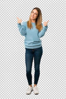 Blondevrouw met blauw overhemd die duimen op gebaar met beide handen en het glimlachen geven