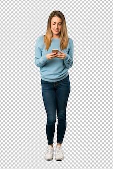 Blondevrouw met blauw overhemd die een bericht met mobiel verzenden