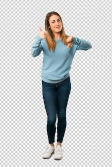 Blondevrouw met blauw overhemd die goedaardig teken maken. onbeslist tussen ja of nee