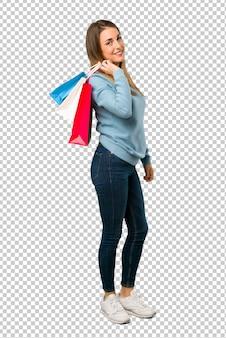 Blondevrouw met blauw overhemd die heel wat het winkelen zakken houden
