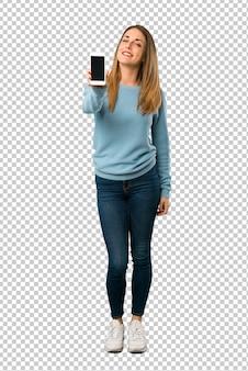 Blondevrouw met blauw overhemd die mobiel tonen
