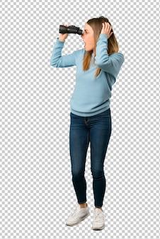 Blondevrouw met blauw overhemd en het kijken in de verte met verrekijkers