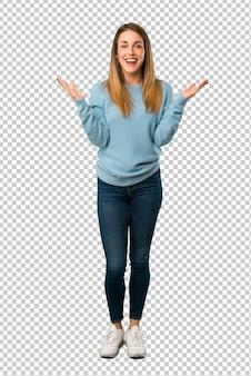 Blondevrouw met blauw overhemd met verrassing en geschokte gelaatsuitdrukking