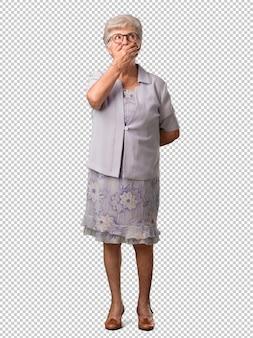 Bocca della copertura della donna senior dell'ente completo, simbolo di silenzio e repressione