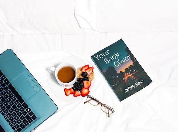 Boek en laptop in bed