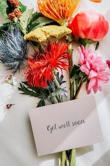 Boeket kleurrijke bloemen op een wit laken met een kaartmodel mock