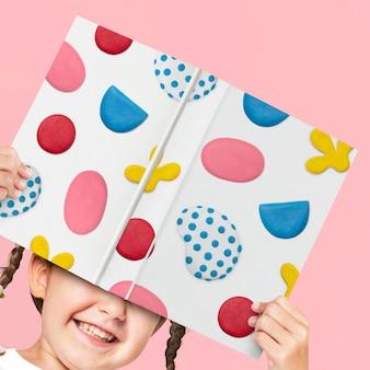 Boekomslag mockup psd met plasticine kleipatroon vastgehouden door een meisje