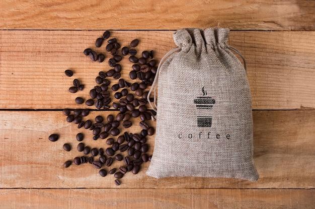 Borsa da caffè con fagioli accanto