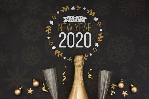 Botella de champán dorado y copas vacías sobre fondo negro