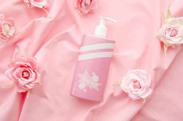 Botella de jabón sobre fondo de tela rosa