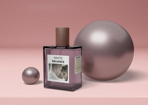 Botella de perfume al lado de bolas en la mesa