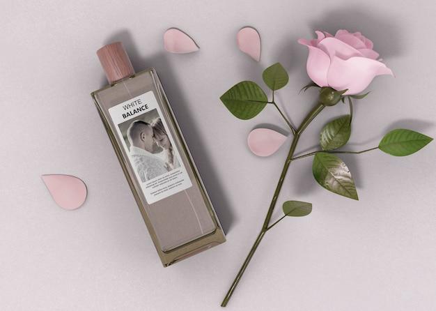 Botella de perfume al lado de rosa en la mesa