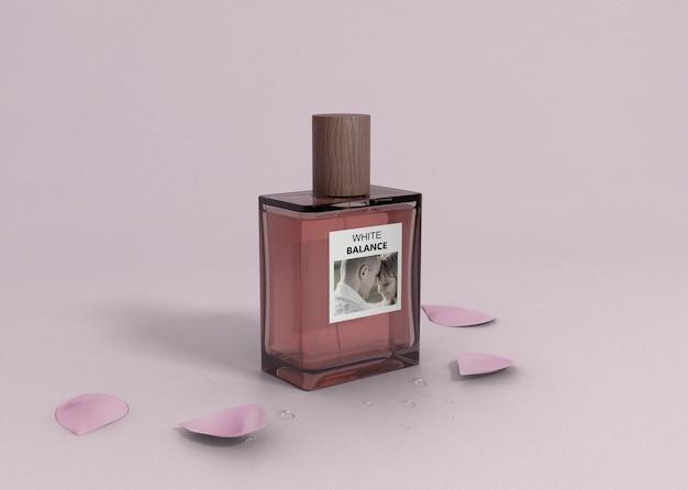 Botella de perfume en mesa con pétalos
