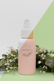 Botella de spray de productos de belleza con planta