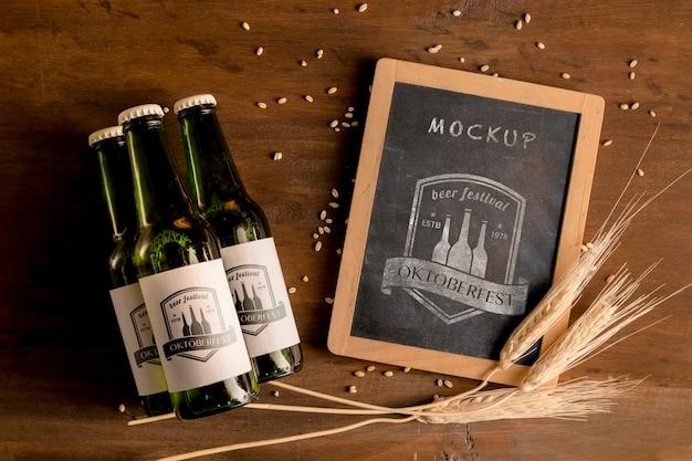 Botellas de cerveza con trigo y marco de maqueta