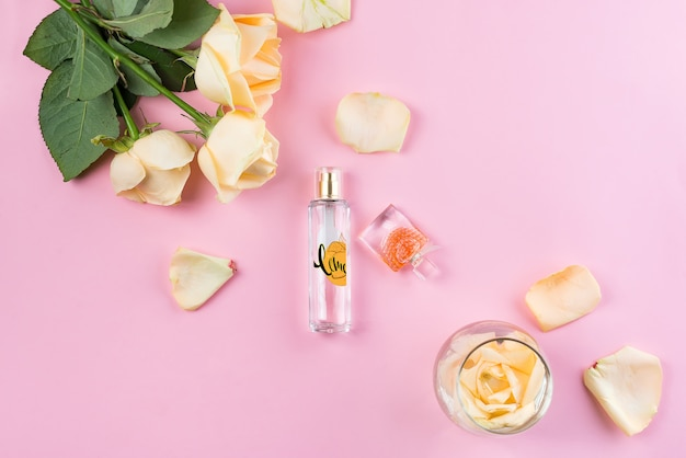 Botellas de perfume con flores sobre fondo rosa
