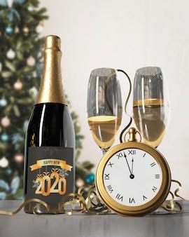 Bottiglia di champagne e bicchieri preparati per il nuovo anno
